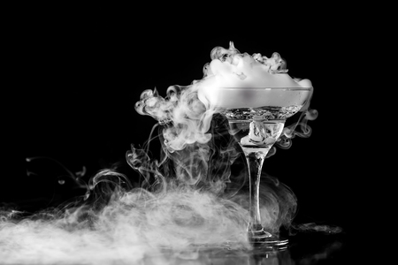 Closeup wine glass with fog at dark background. Chemical reaction of dry ice with water.
