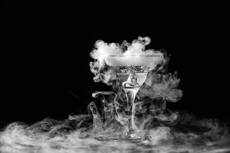 Primer vaso de vino con niebla en fondo oscuro. Reacción química del hielo seco con agua. Foto de archivo