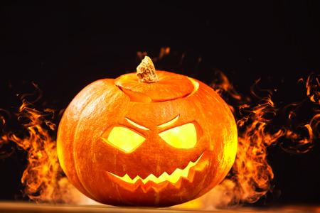 Closeup jack-o-lantern Halloween calabaza con fuego quemando alrededor de fondo oscuro.