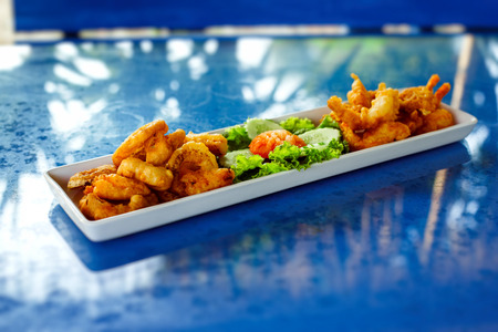A plate with deep-fried spicy golden calamari rings and tasty shrimps with vegetables at blue table background.