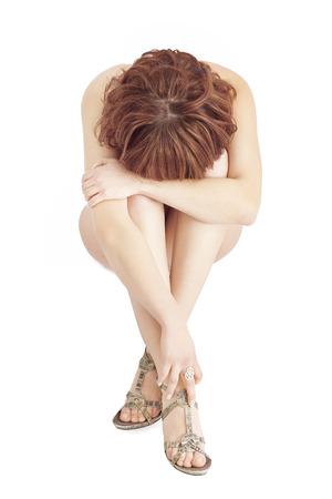 Mujer desnuda sentada en el fondo blanco aislado con las manos cubriendo la cara.