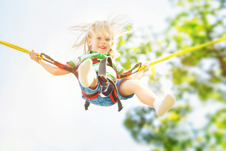 Happy child jumping with a bungee at summer sky background. Фото со стока