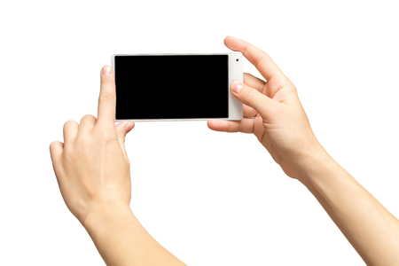 Mockup of female hands holding frameless cellphone with black screen and making selfie at isolated background.