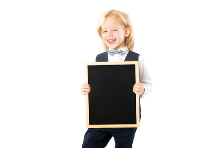 Smart happy child in suit is holding blank blackboard and smiling isolated at white background.