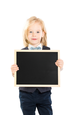 Verical portrait of elegant boy in suit holding blank blackboard isolated at white background.