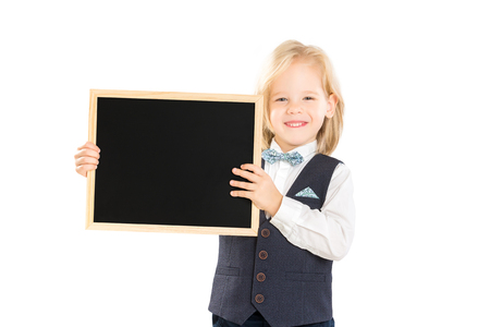 Closeup portrait of elegant smiling boy in suit holding blank blackboard isolated at white background. Banque d'images