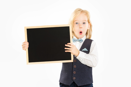 Closeup portrait of surprised child in suit holding blank blackboard isolated at white background.