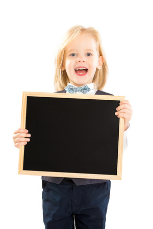 Closeup portrait of cute laughing boy in suit holding black board isolated at white background.