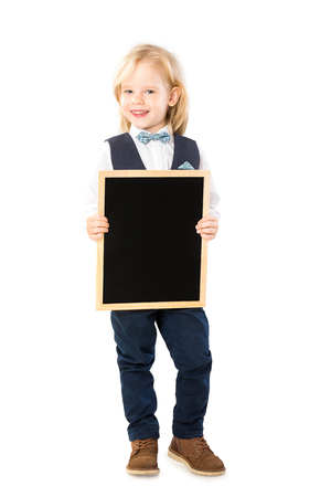 Happy elegant boy in suit is holding blank chalk board isolated at white background. Banque d'images