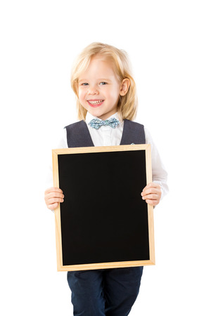Closeup portrait of cute smiling boy in suit holding black board isolated at white background. Banque d'images
