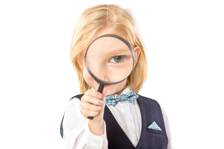 Happy little boy is looking through magnifying glass isolated at white background. Banque d'images