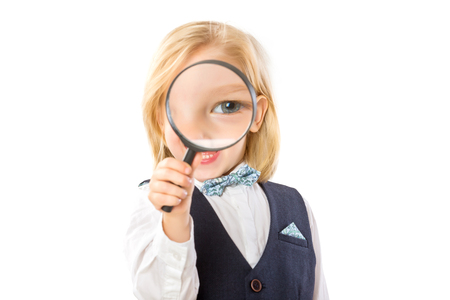 Happy little boy is looking through magnifying glass with distorted eye isolated at white background.