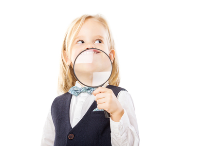 Happy merry boy is holding magnifying glass at his mouth isolated at white background.