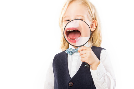 Happy merry boy is holding magnifying glass at his mouth and laughing isolated at white background.