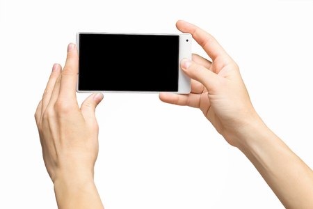 Mockup of female hands holding white frameless cellphone with black screen and making selfie at isolated background. Banque d'images