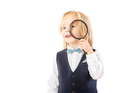 Happy little boy with long hair is looking through magnifying glass like detective isolated at white background. Banque d'images