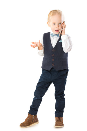 Portrait of smart child in suit talking by cellphone with emotions isolated at white background. Banque d'images