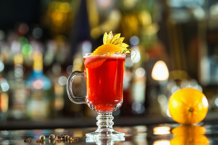 Closeup glass of red cocktail decorated with orange and apple slices at bright bar counter background.