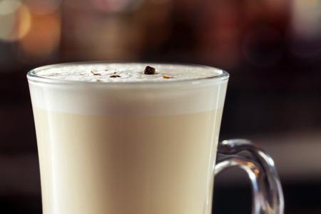 Imagen del primer del cóctel del batido de leche adornado con el chocolate en el fondo brillante borroso.