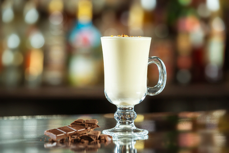 Glass of milk cocktail decorated with chocolate at bar counter background.