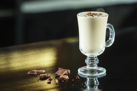 Glass of milk cocktail decorated with chocolate at table background.