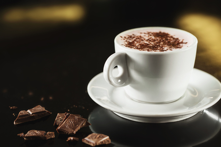 Closeup image of white cup full of latte coffee at dark background.