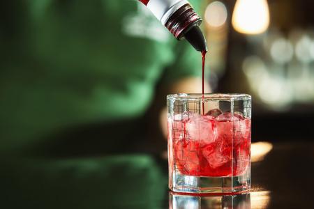Imagen del primer de verter el jarabe del buttle al vidrio de cóctel en el fondo de la barra. Foto de archivo