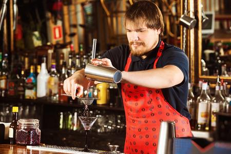 El camarero está vertiendo una bebida alcohólica usando colador y agitador en el fondo de la barra.