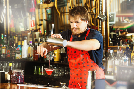 Bartender is pouring alcohol drink using strainer and shaker at bar background.