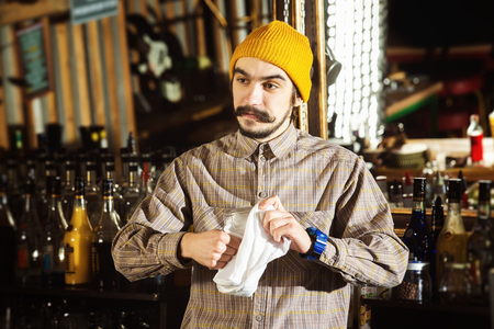 Hipster style barman is cleaning glass with a cloth at bar counter background. Foto de archivo