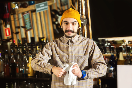 Hipster style barman is cleaning glass with a cloth at bar counter background. Kho ảnh