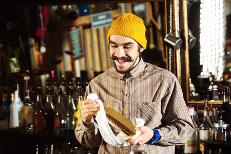 Happy barman is cleaning bottle with a cloth at bar counter background.