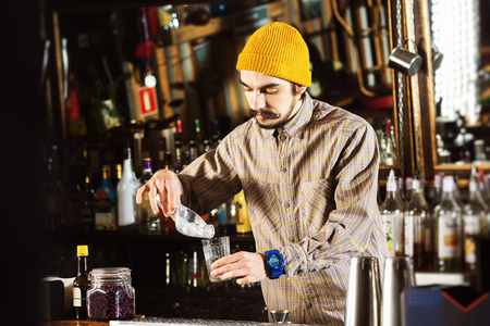 Portrait of hipster barman adding ice cubes to a cocktail at bar background. Kho ảnh