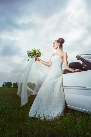 Portrait of happy bride sitting on a car and holding flowers bouquet outdoors at field background.