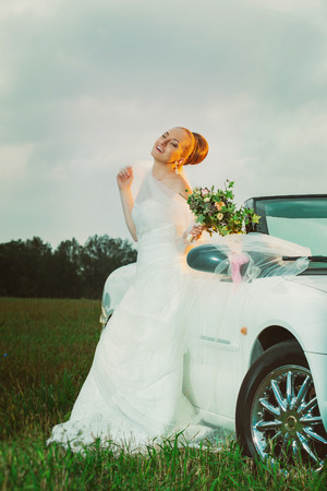 Vertical portrait of happy bride sitting on a car outdoors at field background.