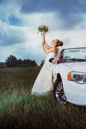 Portrait of happy bride sitting on a car and holding flowers bouquet above head outdoors at field background.