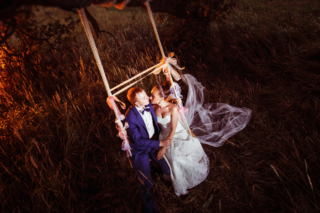 Beautiful married couple is kissing on swing outdoors at rye field background. View from above.