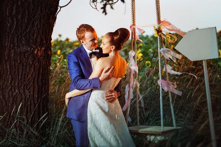El novio elegante está abrazando tiernamente a la novia hermosa en un fondo del campo de los girasoles del verano.