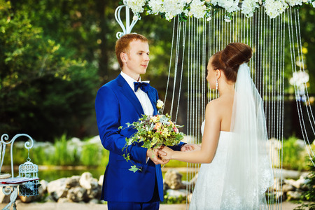 Portrait of beautiful couple holding hands at wedding caremony outdoors at decorated arch background. Kho ảnh