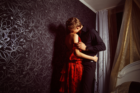 Beautiful young couple is embracing and kissing at bedroom wall background. Kho ảnh