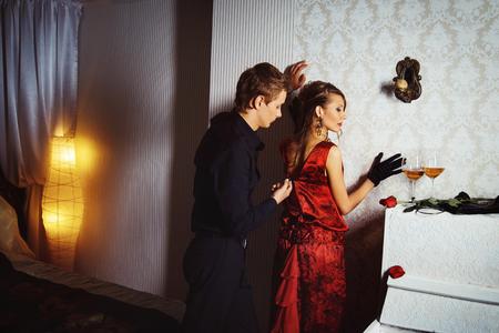 Sexual elegant dressed couple is flirting in bedroom.
