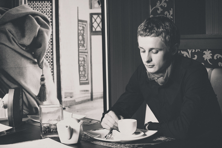 Closeup black and white portrait of man drinking coffee in vintage style cafe.