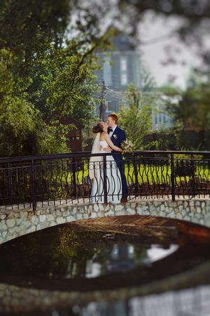 Closeup image of beautiful kissing wedding couple outdoors at summer lake background.