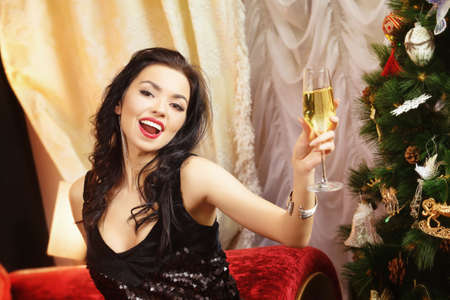 Beautiful woman in black dress is holding champagne glass and laughing at decorated Christmas tree background.