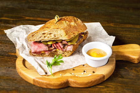 Closeup image of sandwich with meat and cucumbers at wooden board background.
