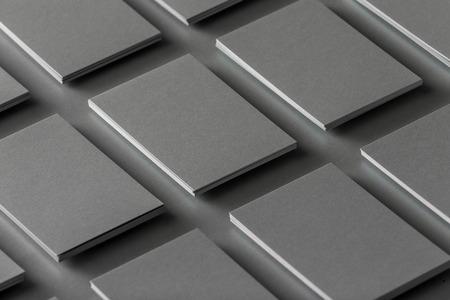 Mockup of horizontal business cards stacks arranged in rows at grey textured paper background.