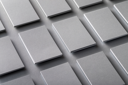 Mockup of vertical business cards stacks arranged in rows at grey textured paper background.