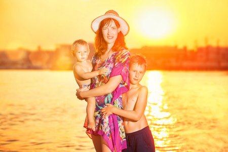 Happy mother is walking with two sons along sea coast at sunset background.