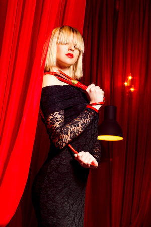 Portrait of sexy stranger women in dress holding a whip at red curtain background.