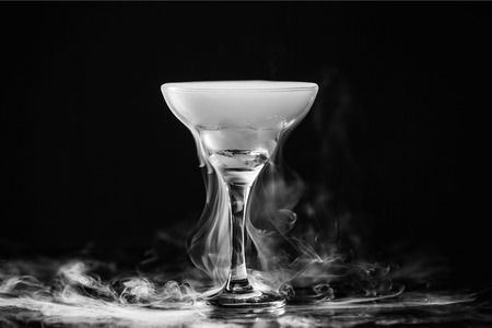 Closeup wine glass with white fog at dark background. Chemical reaction of dry ice with water.
